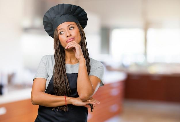 Ritratto di una giovane donna di baker nero che pensa e guarda in alto, confuso su un'idea
