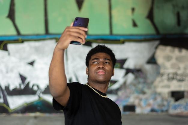 Ritratto di un giovane ragazzo nero che fa una foto di auto con il suo telefono cellulare. sfondo muro di graffiti.