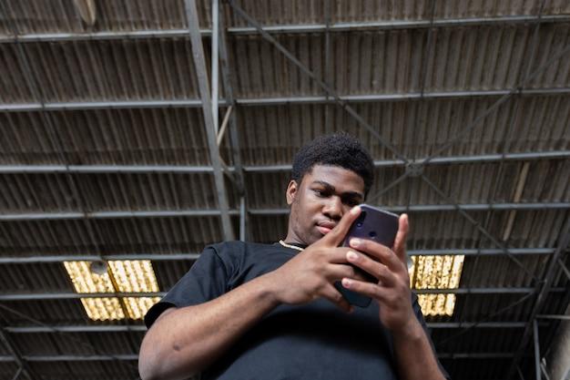 Ritratto di un giovane ragazzo nero utilizzando il suo telefono cellulare. sfondo muro di graffiti.