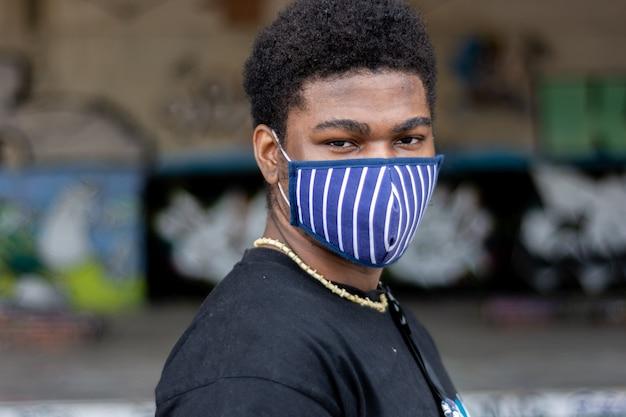 Ritratto di giovane ragazzo nero con maschera facciale. sfondo muro di graffiti.