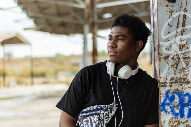 Ritratto di giovane ragazzo nero con cuffie bianche. ascoltare la musica. sfondo di edificio abbandonato.