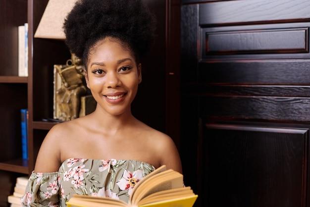 Ritratto di una giovane studentessa nera. è in piedi nella biblioteca dell'università, tiene in mano un libro e guarda la telecamera.