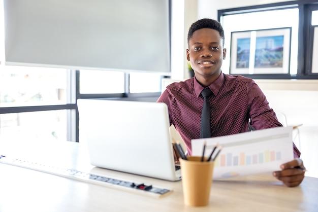 Ritratto di un giovane uomo di colore che utilizza un laptop in un ambiente di lavoro, un uomo d'affari africano o uno studente.