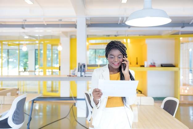 Ritratto di una giovane donna di colore che sorride mentre usa il suo telefono in un ambiente professionale, un uomo d'affari africano o uno studente