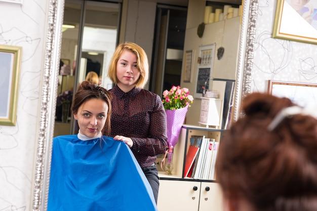 Ritratto di giovane stilista biondo in piedi dietro il giovane cliente femmina bruna che indossa grembiule blu e seduto in poltrona in salone - riflesso nel grande specchio