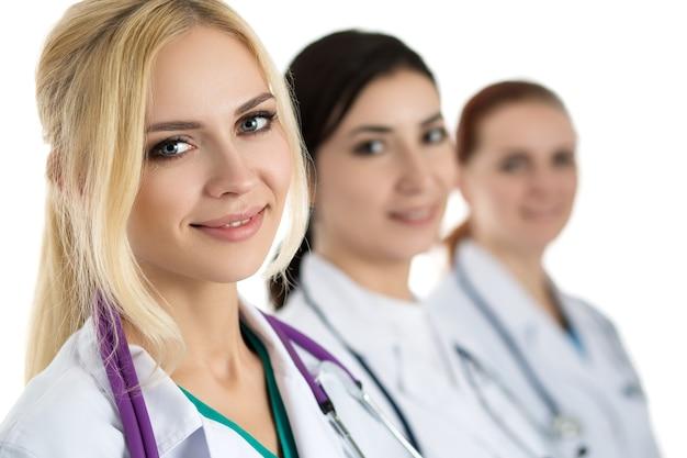 Ritratto di giovane donna bionda medico circondato da equipe medica, guardando e sorridente. concetto di sanità e medicina.