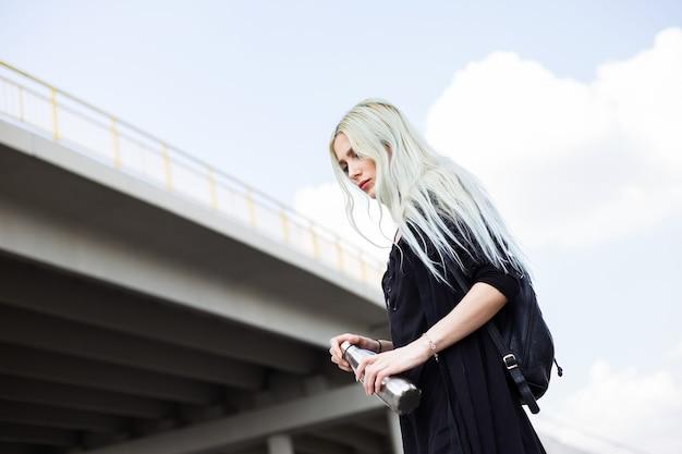 Ritratto di giovane ragazza bionda, vestita di nero con zaino, tenendo in mano una bottiglia termica in acciaio, sotto il ponte moderno.