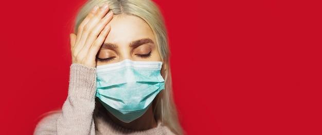 Ritratto di giovane ragazza bionda con mal di testa, tenendo la mano sulla testa, indossando maschera facciale medica