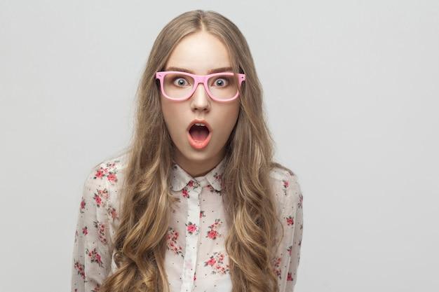 Ritratto giovane ragazza bionda, che guarda l'obbiettivo, con faccia sorpresa e bocca aperta. studio girato, isolato su sfondo grigio