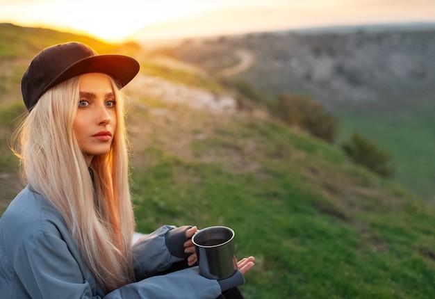 Ritratto di giovane ragazza bionda con cappuccio nero, tenendo la tazza in acciaio con tè caldo sul tramonto con lo spazio della copia.