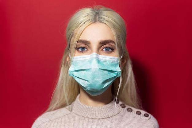 Ritratto di giovane ragazza bionda con gli occhi azzurri, indossando maschera antinfluenzale e maglione