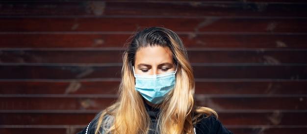 Ritratto di giovane ragazza bionda con gli occhi chiusi, indossando maschera facciale medica