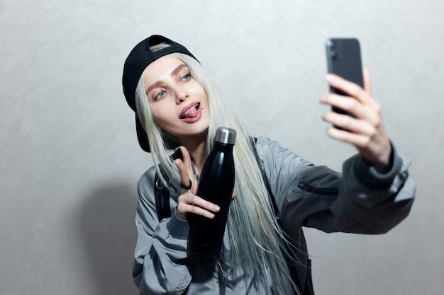 Ritratto di giovane ragazza bionda con bottiglia termica in mano scattare una foto selfie su smartphone.
