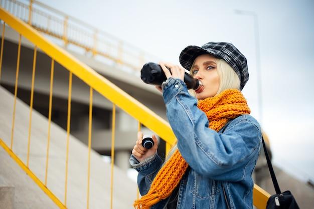 Ritratto di giovane bionda ragazza adolescente acqua potabile dalla bottiglia in acciaio termo eco