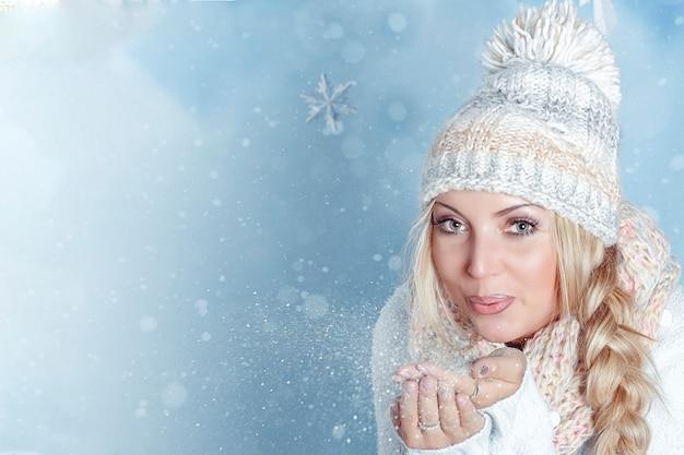 Ritratto di una giovane bionda con gli occhi chiari in un cappello invernale e sciarpa che soffia neve tremolante dalla sua mano