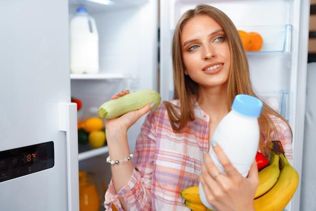 Ritratto di una giovane donna bionda che prende il cibo dal suo frigorifero