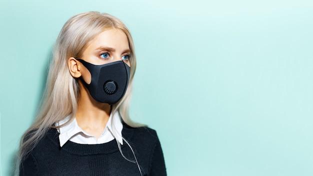Ritratto di giovane donna bionda vestita di nero maschera medica sulla superficie ciano