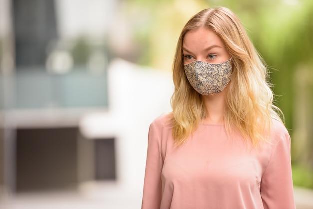 Ritratto di giovane donna bionda con maschera per la protezione dallo scoppio del virus corona nelle strade della città con la natura all'aperto