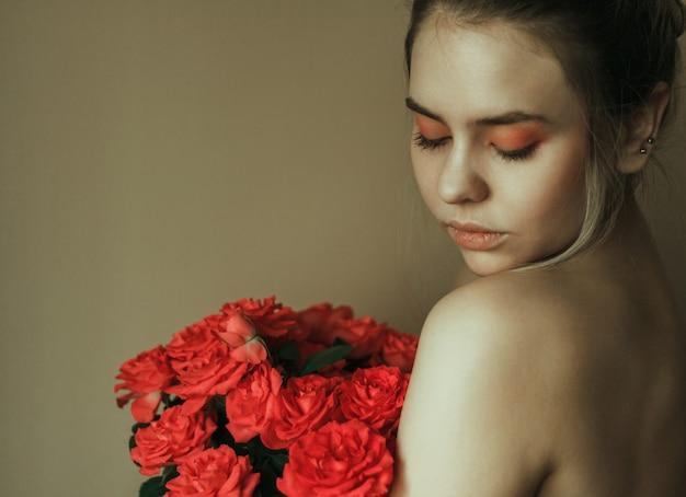 Ritratto di una giovane donna bionda con trucco rosso e un mazzo di rose