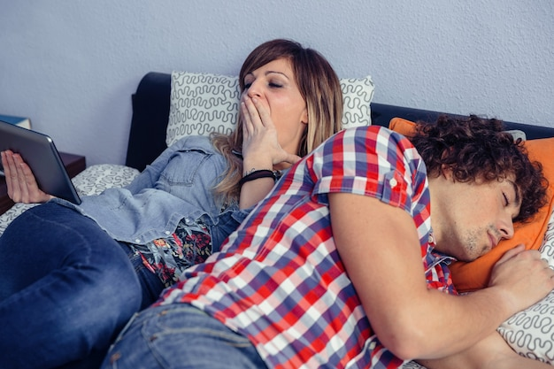 Ritratto di giovane donna annoiata che guarda una tavoletta elettronica e sbadiglia mentre un bell'uomo dorme sdraiato sul letto