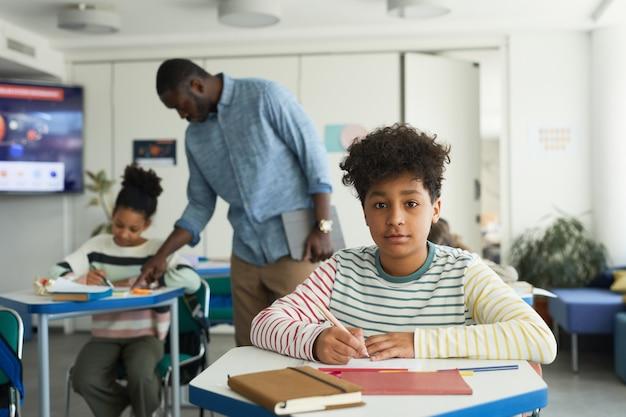 Ritratto di giovane ragazzo seduto alla scrivania in aula scolastica e guardando la telecamera, copia spazio