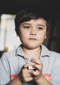 Ritratto di giovane ragazzo in piedi da solo tenendo i soldi con la faccia pensante