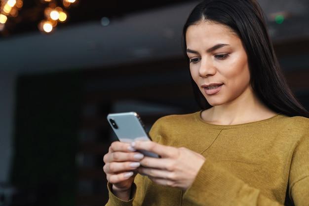 Ritratto di giovane imprenditrice caucasica bruna che utilizza il cellulare mentre si lavora in ufficio