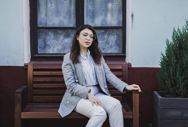 Ritratto di giovane ragazza bruna capelli lunghi seduto sulla strada