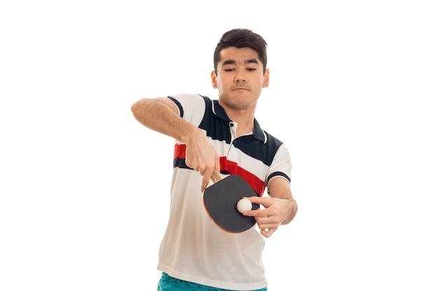 Ritratto di giovane uomo bruna giocando a ping-pong isolato sul muro bianco in studio