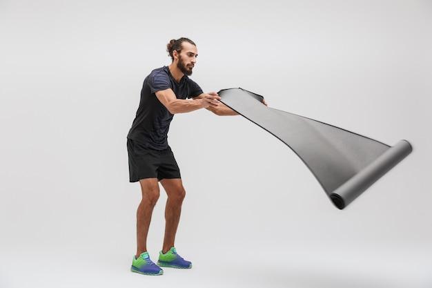 Ritratto di giovane sportivo bruna in tuta da ginnastica che tiene tappetino da yoga mentre si fa allenamento isolato su bianco