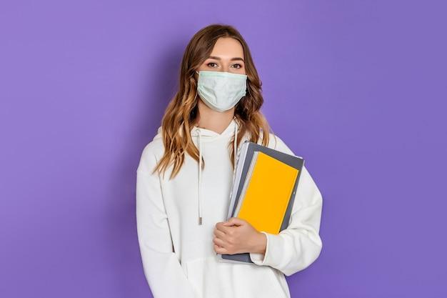 Ritratto di giovane studentessa bruna con maschera medica chirurgica che indossa una felpa con cappuccio bianca in piedi e guardando la telecamera isolata su sfondo lilla
