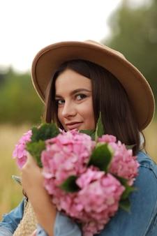Ritratto di una giovane donna bruna in giacca di jeans e cappello azienda bouquet di fiori rosa ortensie,