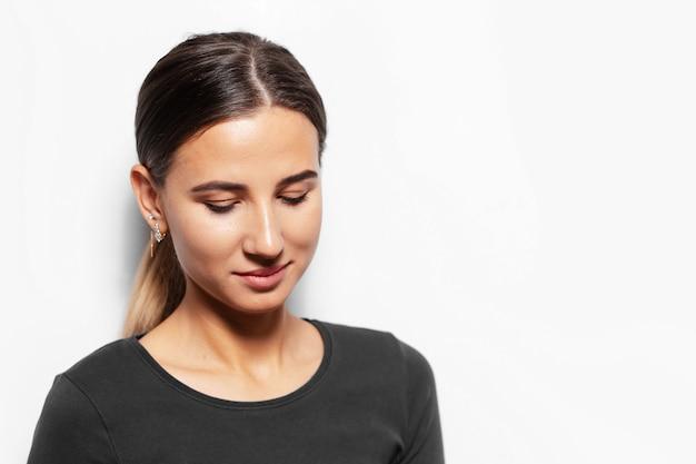 Ritratto di giovane donna bruna guardando verso il basso.