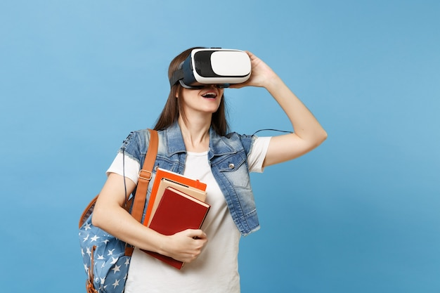 Ritratto di giovane studentessa bruna in abiti denim con zaino che indossa cuffie da realtà virtuale che tiene libri scolastici isolati su sfondo blu. istruzione al college universitario di scuola superiore.