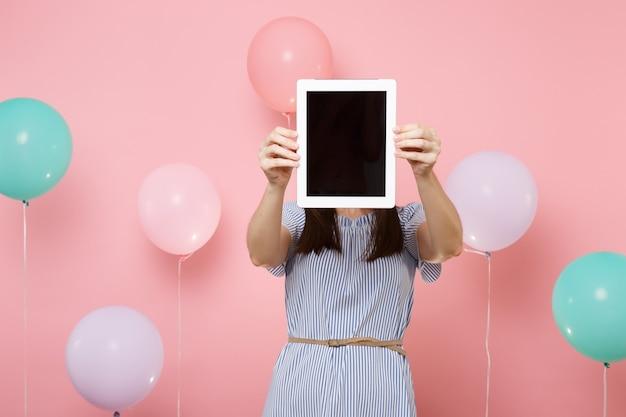 Ritratto di giovane donna castana che indossa vestito blu che tiene il viso coprente con computer tablet pc con schermo vuoto vuoto su sfondo rosa con mongolfiere colorate. concetto di festa di compleanno.