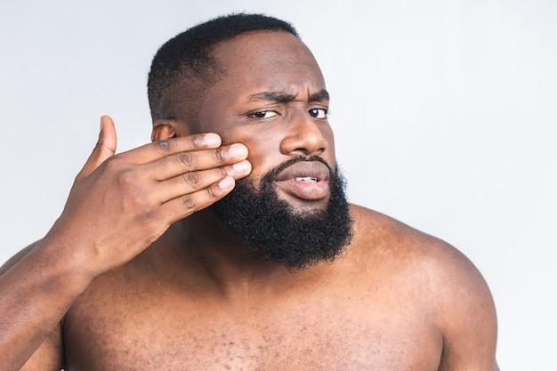 Ritratto di giovane uomo di colore afroamericano brutale che applica crema facciale sulla sua guancia isolata sopra fondo bianco. ritratto ravvicinato, bellezza maschile. cura della pelle