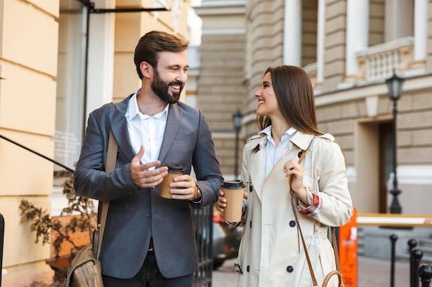 Ritratto di giovane coppia d'affari uomo e donna in abbigliamento formale bevendo caffè da asporto e parlando insieme mentre si cammina per le strade della città