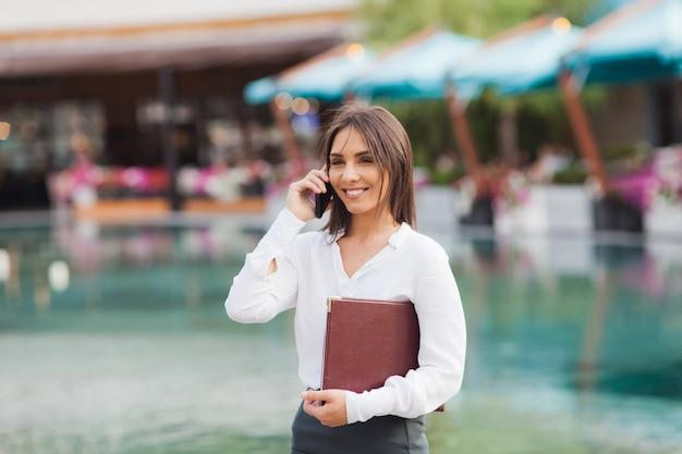 Il ritratto di giovane signora di affari si è vestito in una camicetta bianca all'aperto
