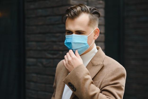 Ritratto di giovane uomo d'affari in una maschera usa e getta