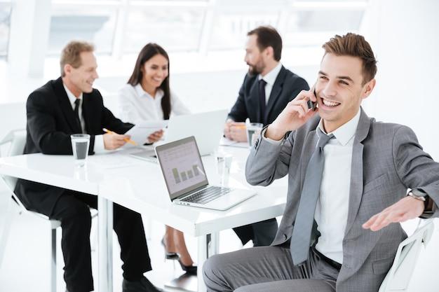 Ritratto di giovane uomo d'affari seduto al tavolo con i colleghi e parlando al telefono