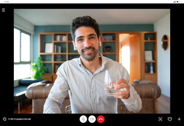 Ritratto di giovane uomo d'affari su una videochiamata di lavoro e in possesso di una tazza di vino durante il soggiorno a casa