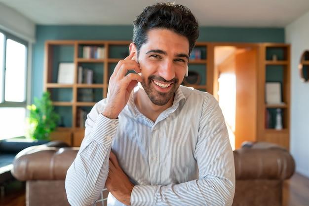 Ritratto di giovane uomo d'affari su una videochiamata di lavoro durante il soggiorno a casa. ufficio a casa.