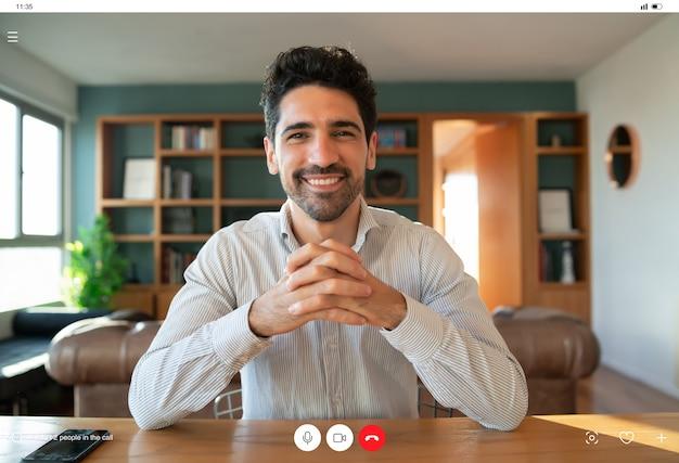 Ritratto di giovane uomo d'affari su una videochiamata di lavoro durante il soggiorno a casa