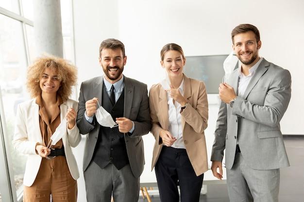 Ritratto di giovani imprenditori togliendosi le maschere protettive in ufficio
