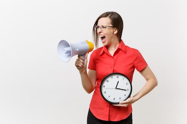 Il ritratto di giovane donna dell'insegnante di affari in camicia rossa che tiene l'orologio rotondo, grida in megafono, annuncia la vendita di sconti, isolata su fondo bianco. notizie calde, concetto di comunicazione... sbrigati, ragazzi