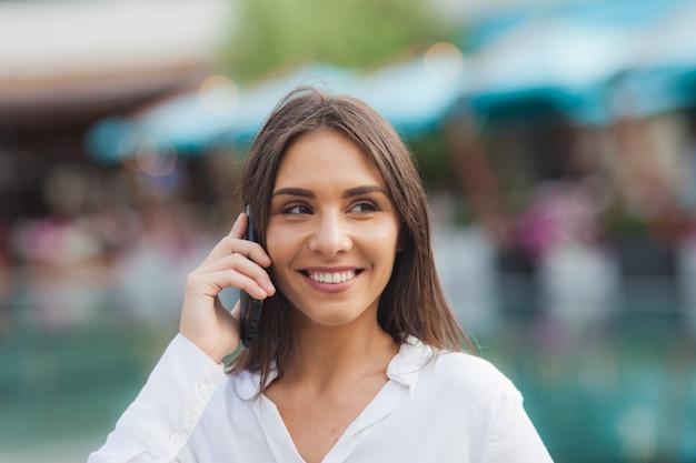 Il ritratto di una giovane donna di affari si è vestito in una blusa bianca mentre parlava al telefono all'aperto