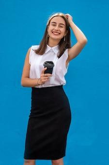 Ritratto di giovane donna d'affari che tiene tazza di caffè isolata su blue