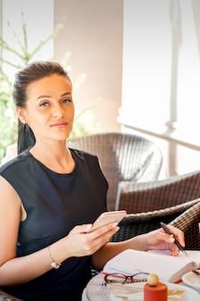 Ritratto di giovane donna d'affari rende note in notebook da smartphone lavorando in pausa caffè nella caffetteria