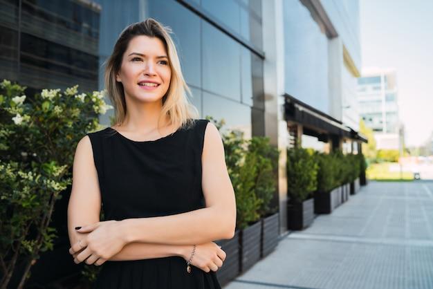 Ritratto degli edifici per uffici esterni diritti della giovane donna di affari. concetto di business e successo.