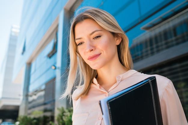 Ritratto di giovane donna d'affari in piedi al di fuori degli edifici per uffici. concetto di affari e successo.